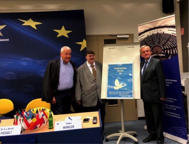 Das Bild zeigt v.l.n.r.: Dr. Ludwig Spaenle, Bernd Posselt und Szabolcz Fazakas am Ende der Veranstaltung vor einem Originalplakat des Paneuropäischen Picknicks.